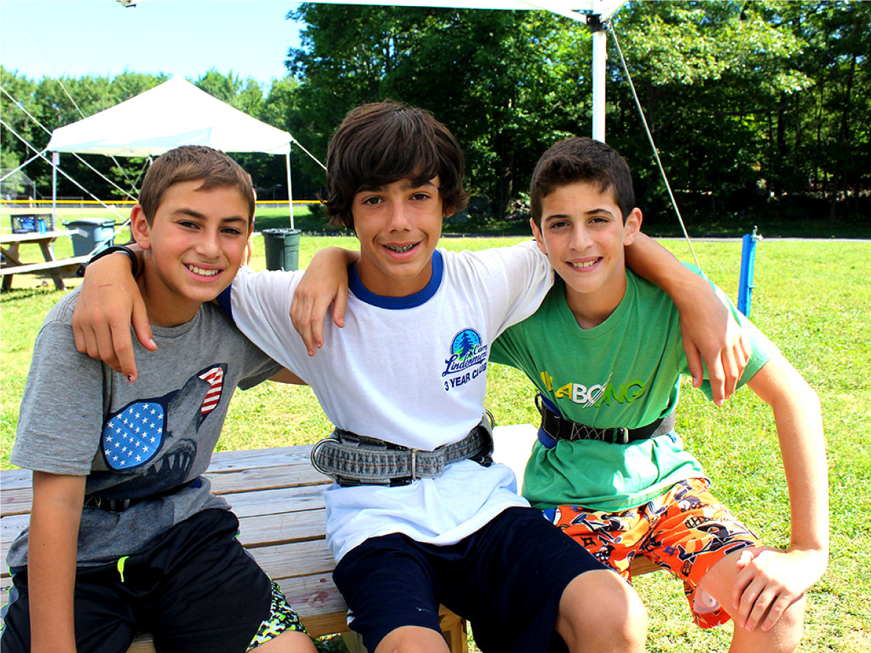 Three male campers by flying trapeze smiling