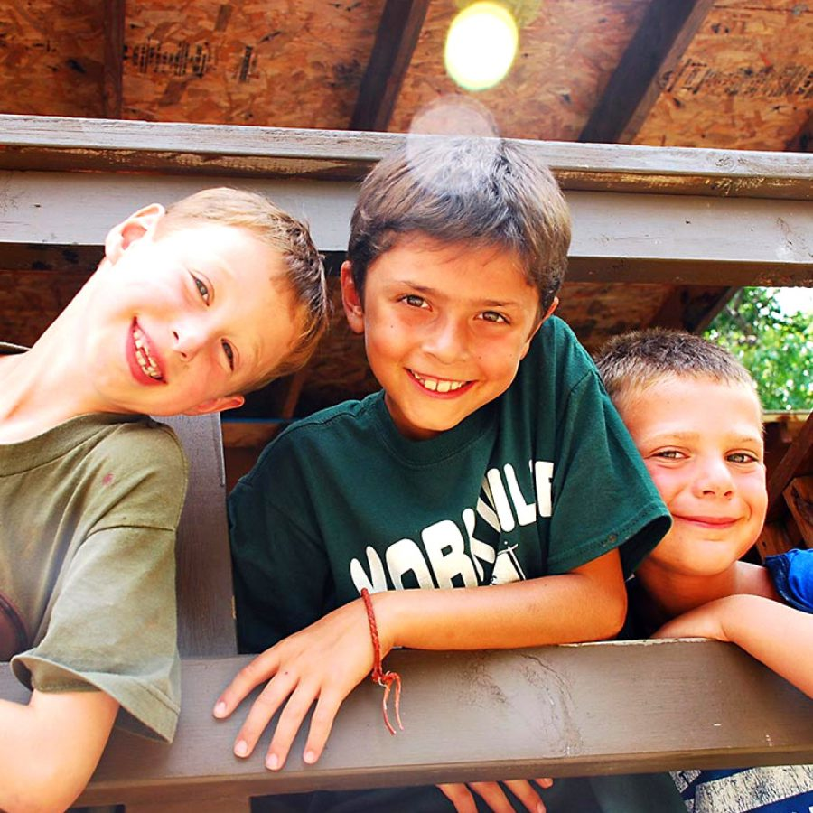 Three male campers on cabin porch