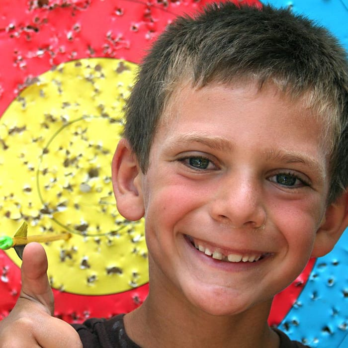boy camper smiling in front of archery target