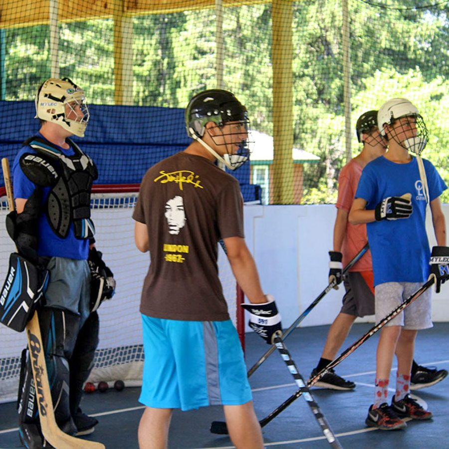Male campers playing street hockey