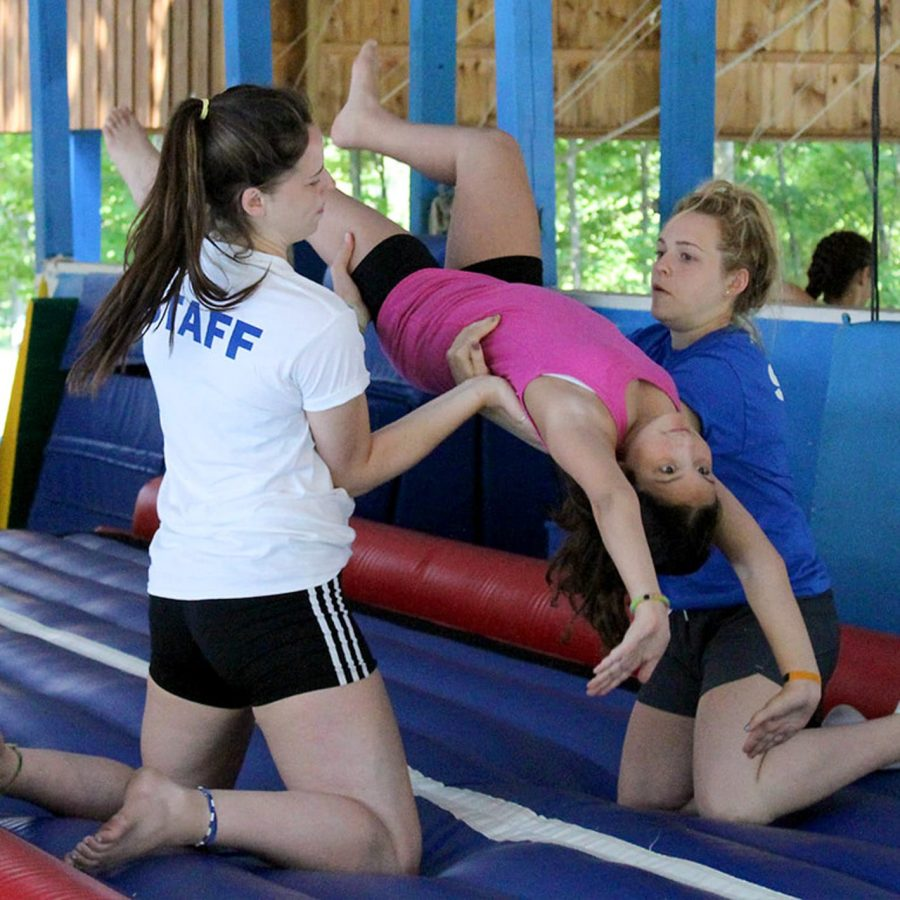 Staff helping a camper in gymnastics