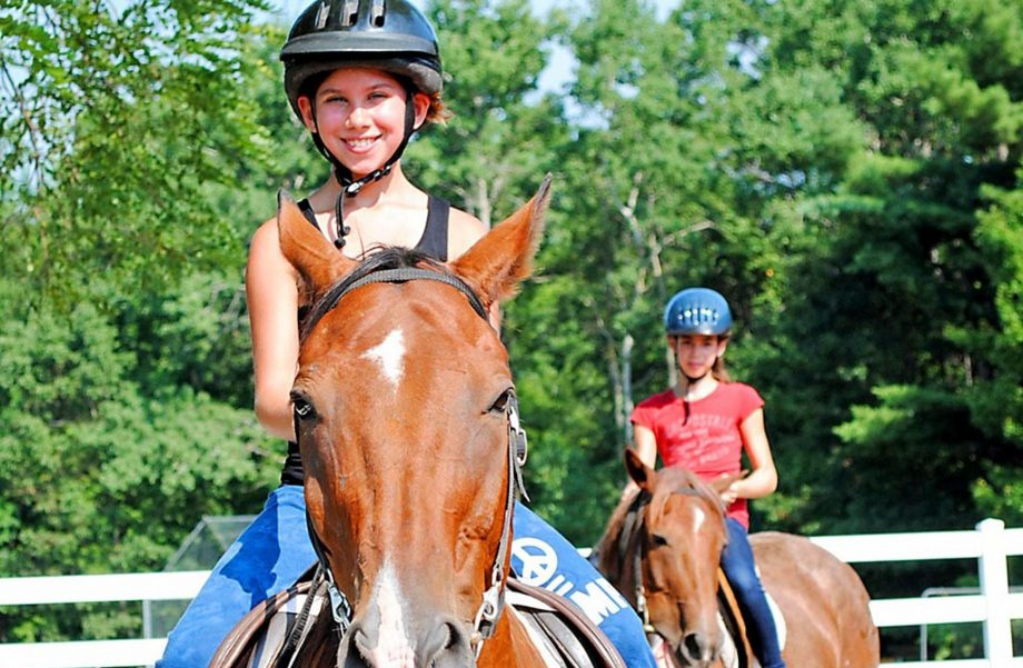 Girls horseback riding in ring