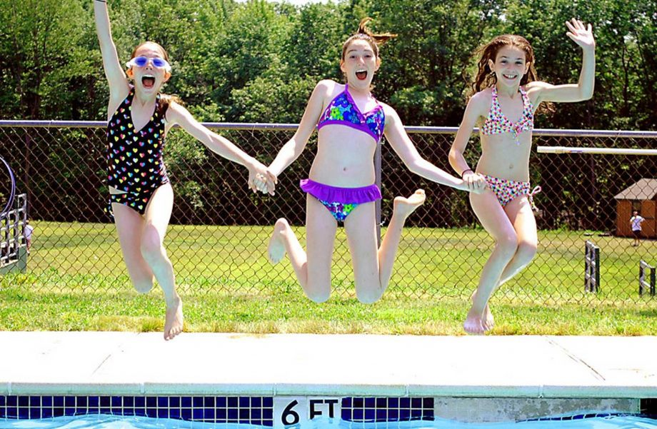 Girls holding hands and jumping into pool