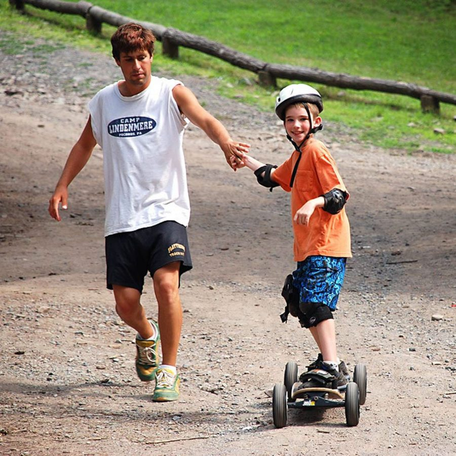 Staff helping camper on mountain board