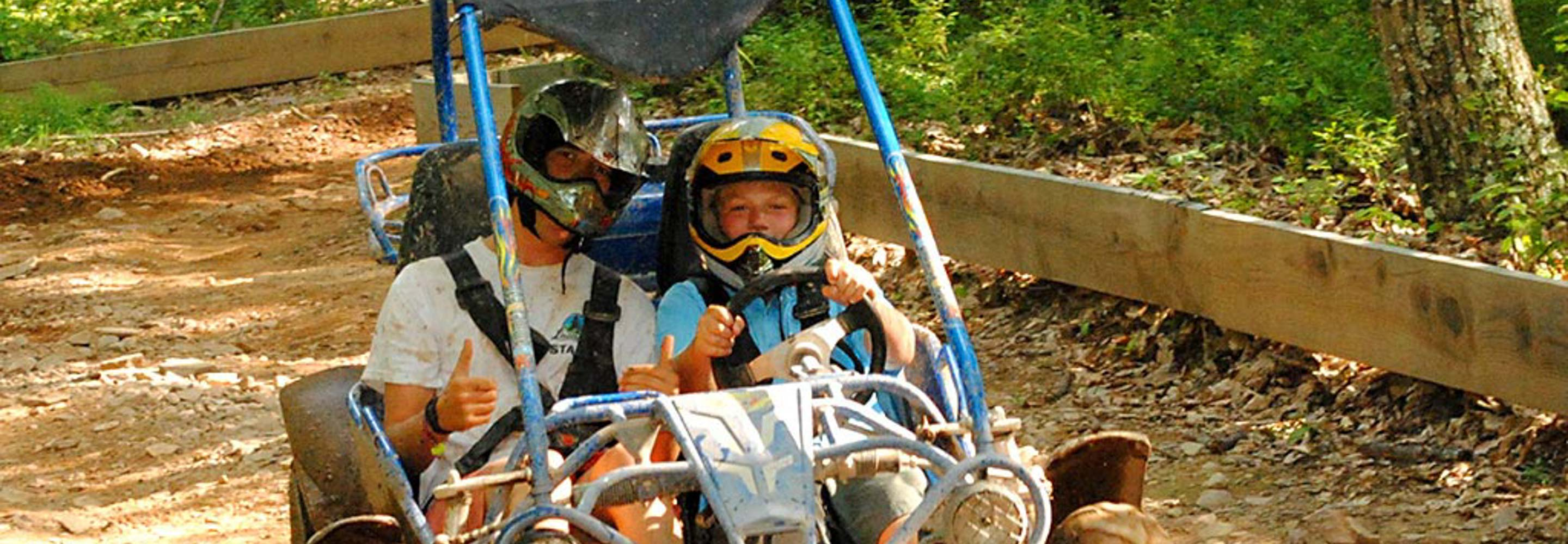 camper and staff riding go kart