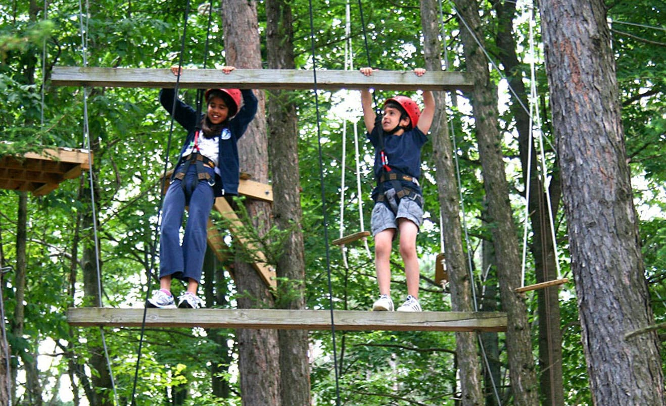 Campers on ropes course ladder during Rookie Days