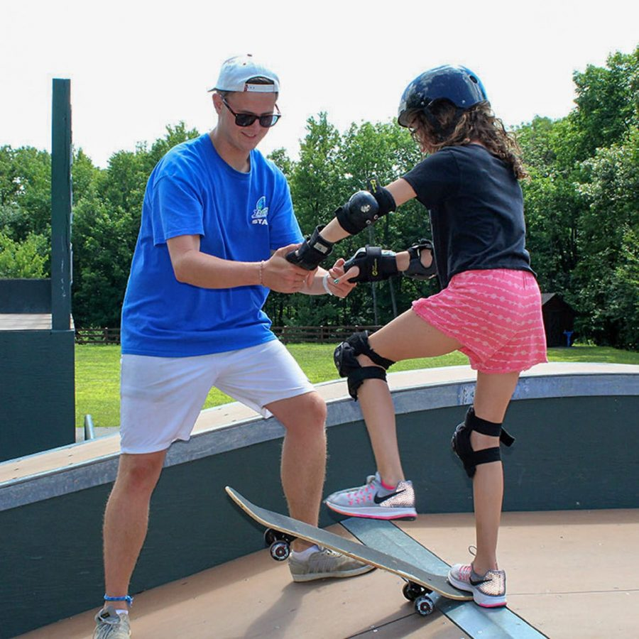 girl camper skateboarding with instructor