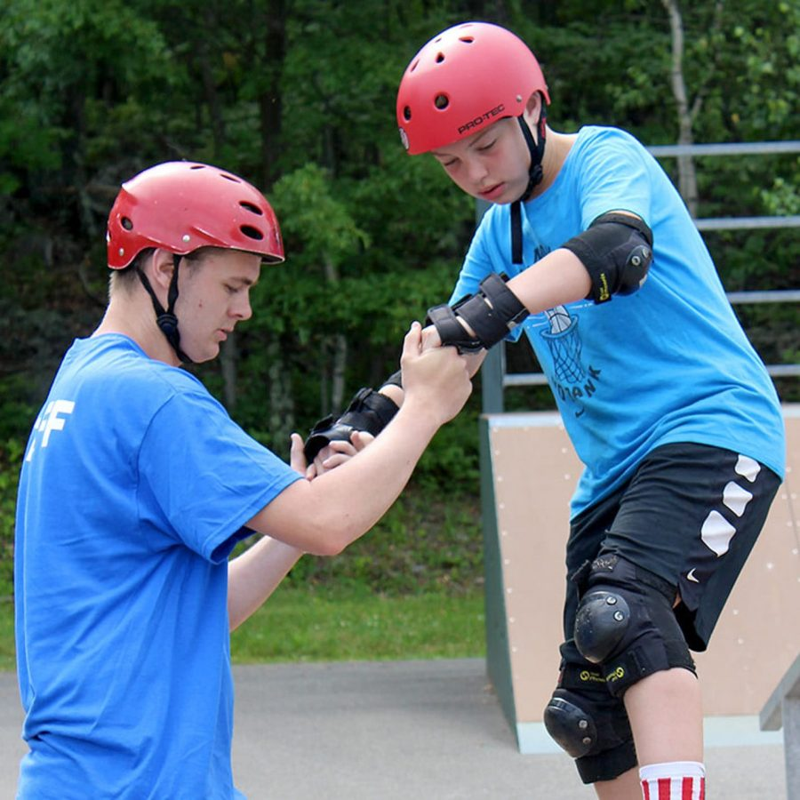Staff helping camper learn to skateboard