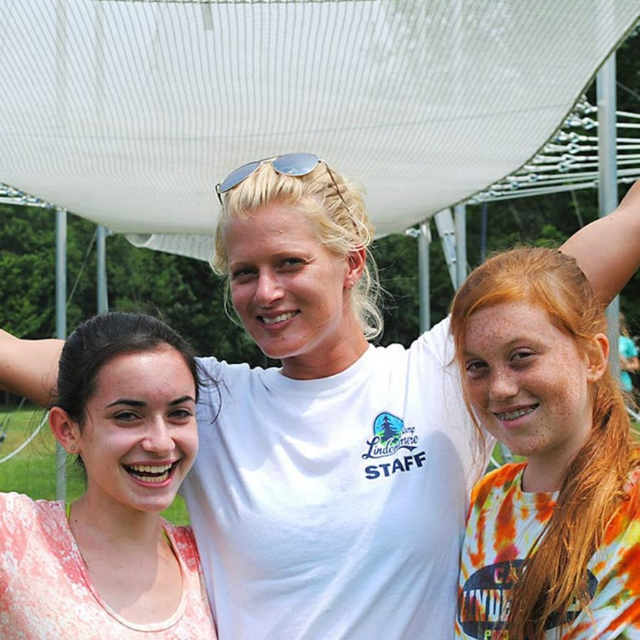 Female staff and campers smiling