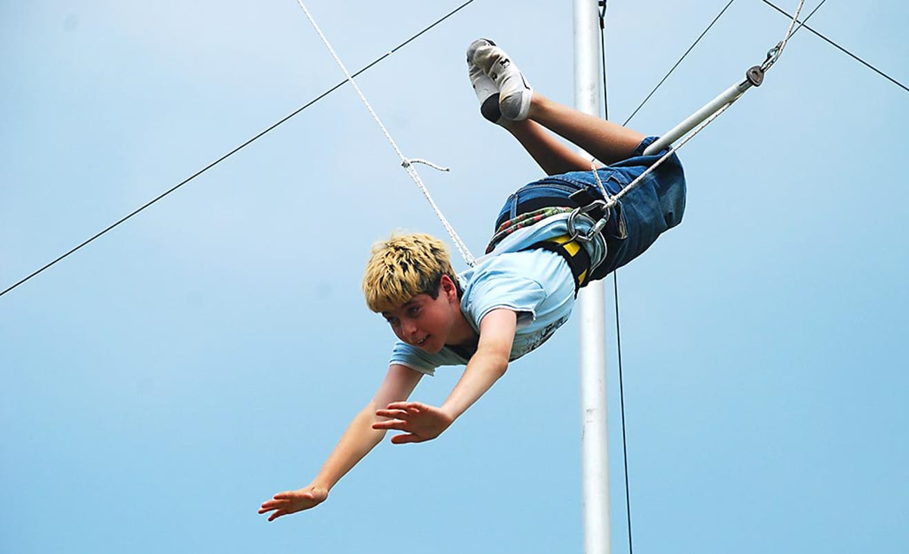 Male camper on flying trapeze